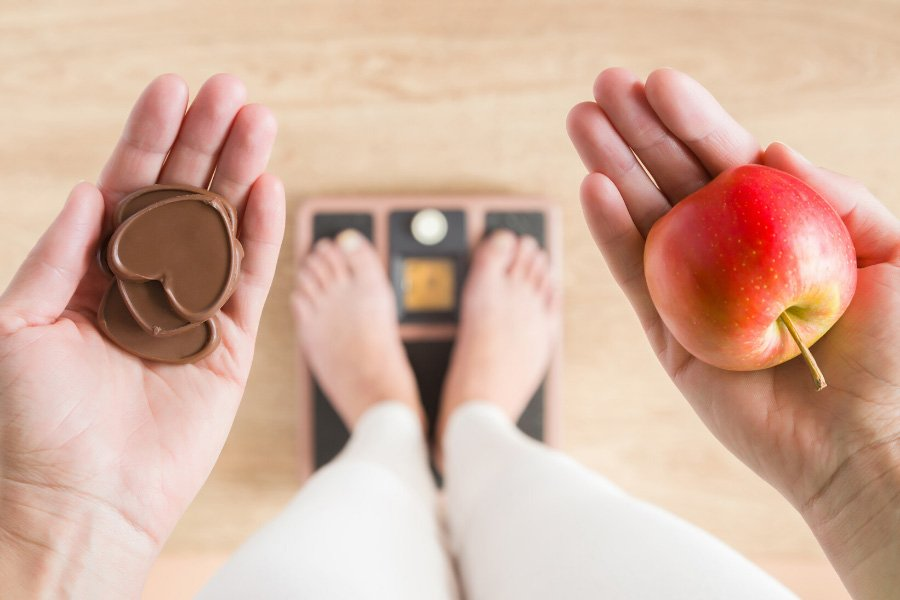 A person standing on a scale while holding chocolate in one hand and an apple in the other